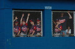 Little League Dugout with kids. Little league baseball kids in the dugout cheering for their teammates during the game stock photo