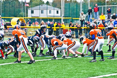 Little League Football Scrimmage Line. A young quarterback calling the play on the line during a little (youth) league football game.  A team of 7-8-9 year old Royalty Free Stock Photos