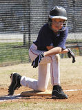 Little league player. A little league baseball player kneeling down on third base stock image