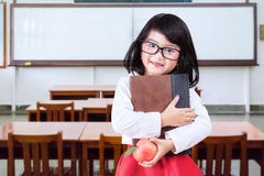Little learner holds book and apple in class Stock Images