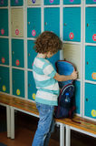 Little learner standing in the hall near the lockers and searching for something in his backpack. Stock Image
