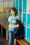 Little learner standing near lockers in school hallway Royalty Free Stock Image