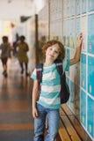 Little learner standing near lockers in school hallway Stock Photo