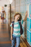Little learner standing near lockers in school hallway. He put his hand on my locker. The boy with a wistful smile, looking at the camera stock photography