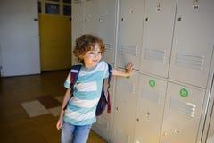 Little learner standing near lockers in school hallway Royalty Free Stock Photos