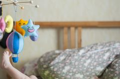 Little leg. Baby in parents bed. Colorful and funny mobile toys stock photo