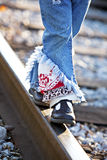 Little legs and feet walking on railroad track. Cute little girl's legs balancing on railroad tracks wearing ripped multi-colored jeans Stock Photography