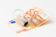 Little light bulb is laying on money Royalty Free Stock Photo