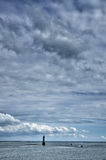 Little lighthouse with cloudy sky on background Stock Images