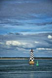 Little lighthouse with cloudy sky on background Royalty Free Stock Photos