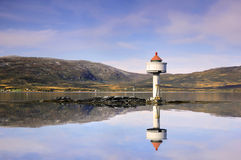 Little lighthouse reflected in the Norwegian fjord Stock Photography
