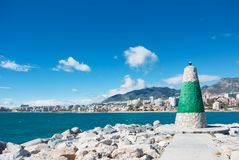 A little lighthouse of white and green color at the pier covered. With stones and bright blue water, beach and hotels at the background. Copy space for text royalty free stock image