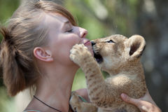 Little lion cub biting girl playing Royalty Free Stock Images
