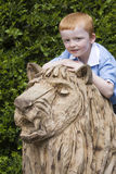 Little lion tamer. Small boy on top of a sculptured lion Stock Images
