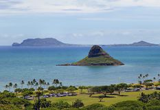 Little Lizard. Chinaman's Hat rises as a rock formation from the sea floor Royalty Free Stock Photo