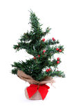 Little Lonely Artificial Christmas Tree. With red berries on it, trunk is wrapped in burlap material tied with a red bow Royalty Free Stock Photo
