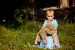 Little lonely boy with teddy bear. Little boy sitting on a prop, holding his teddy bear, looking sad and lonely, forgotten Royalty Free Stock Photography
