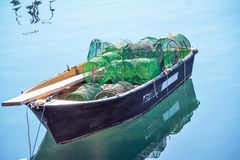 Little lonely fish boat with nets. Inside on a turquoise sea , pozzuoli port, naples, italy stock photo
