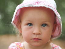 Little lonely girl. With blue eyes and pink hat looking sadly into the camera royalty free stock images