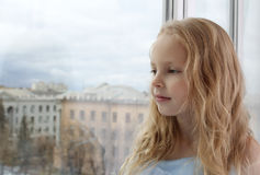 Little lonely girl looking out the window. The girl blonde. The child dreamy face. Outside, cityscape Royalty Free Stock Image