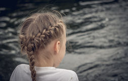 Little lonely girl at the river. Little girl  resting on the river Bank. Loneliness and sadness Royalty Free Stock Images