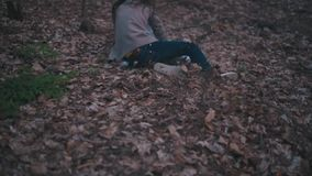 Little lost girl with a bright scarf running through the dark forest, she is frightened and lonely, she falls down, gets stock footage