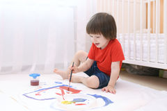 Little lovely child paints with brush and gouache Stock Photography