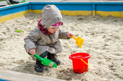 Little lovely girl baby playing in the sandbox on the playground with a shovel and bucket digging a hole, dressed in a raincoat wi Stock Photos