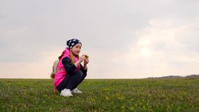 The little lovely girl collects flowers on a green meadow stock video footage