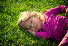 Little lovely girl playing on the grass in the park. filtered image. Royalty Free Stock Image