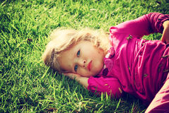Little lovely girl playing on the grass in the park. filtered image. Stock Photography