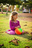 Little lovely girl playing with her ball on the grass in the park. filtered image. Royalty Free Stock Photos