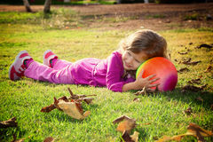 Little lovely girl playing with her ball on the grass in the park. filtered image Royalty Free Stock Images