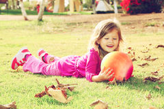 Little lovely girl playing with her ball on the grass in the park. filtered image. Royalty Free Stock Photography