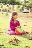 Little lovely girl playing with her ball on the grass in the park. filtered image. Royalty Free Stock Images