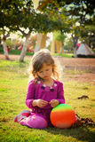 Little lovely girl playing with her ball on the grass in the park. filtered image Stock Photography