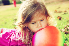 Little lovely girl playing with her ball on the grass in the park. filtered image Royalty Free Stock Photos