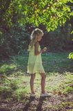 Little lovely girl in yellow dress standing under the tree. Beautiful caucasian girl with long blond hair in yellow dress standing under the tree in summer time Royalty Free Stock Photo