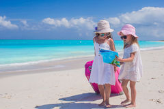 Little lovely girls with big suitcase and a map on tropical beach Stock Images