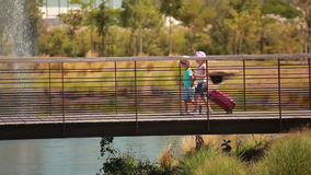 Little lovely kids cross bridge with a suitcase. Little lovely kids hold hands and cross bridge with a suitcase stock video footage