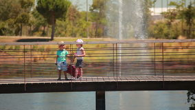 Little lovely kids hold hands and cross bridge. With a suitcase stock video footage