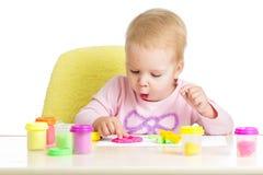 Little lurar att sitta på tabellen som leker med lera royaltyfria bilder