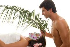 Little Luxuries. Indulgence!  A young woman is gently fanned with a palm frond at a luxury  day spa, exotic beauty salon, holiday resort, or perhaps she is Stock Photos