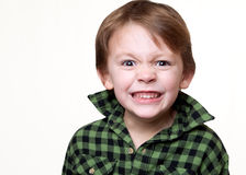 Little mad kid. Young boy making an angry face on a white background Stock Photos
