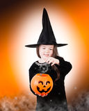 A Little Magic. A young witch uses her magic to brew something up in her jack o'lantern Stock Image