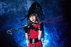 Little magician. Beautiful little girl in a costume of witch posing with broom over dark background Royalty Free Stock Photo