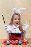Little magician girl conjuring easter items Stock Photo