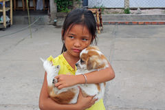 Little Malaysian girl and a dog. Little girl with the dog in Malaysia, Asia Royalty Free Stock Image