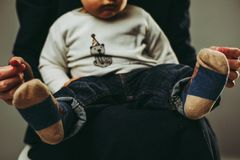 Horizontal portrait of baby sitting on mother`s laps. Little male toddler sitting on mother`s laps, wearing casual clothing, without faces, family portrait Royalty Free Stock Photography