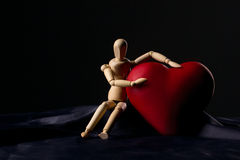 Little man with big heart. Little wooden man sitting and holding  big red heart on dark background Stock Photo